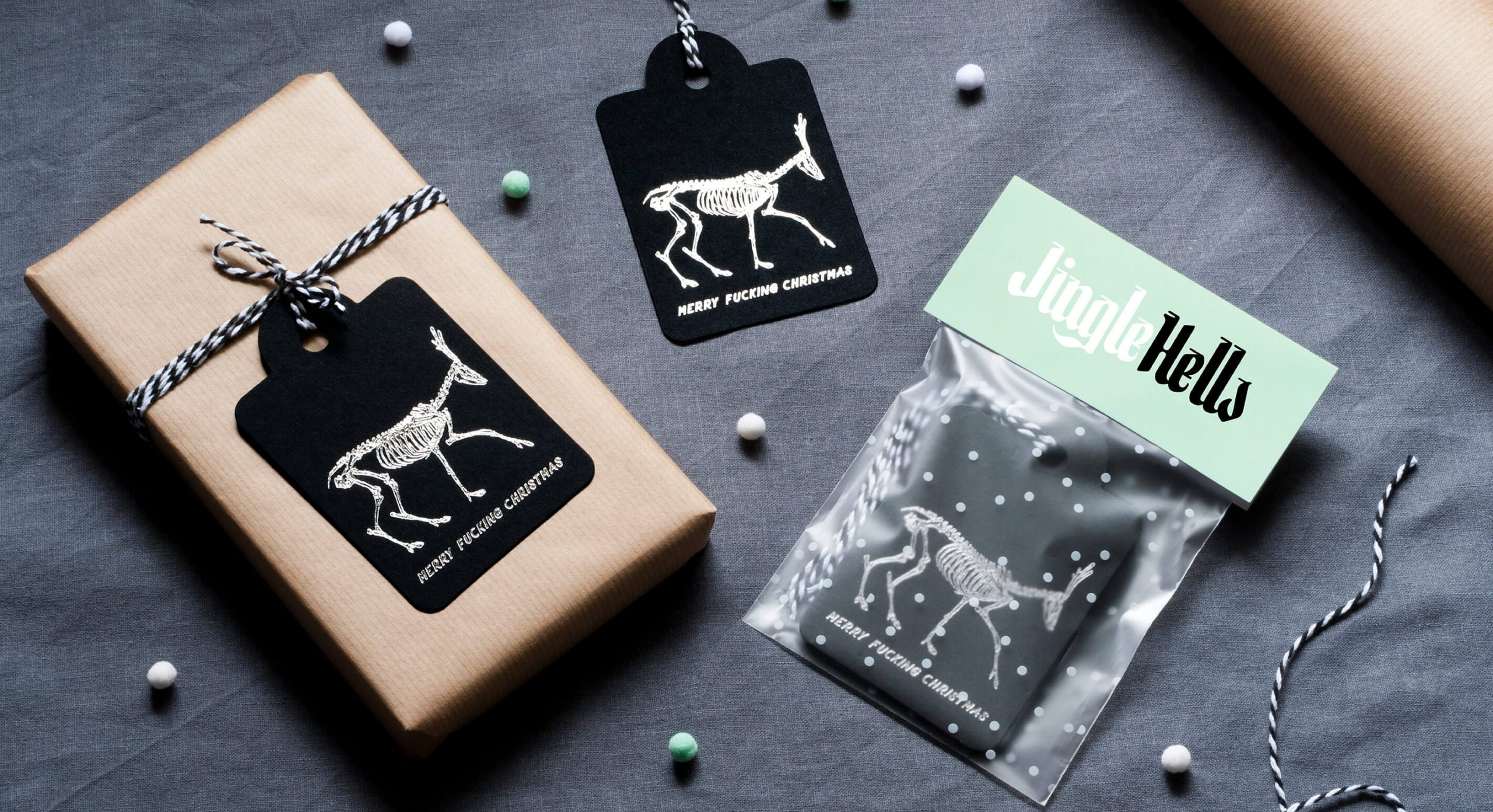 Product flaylay showing alternative foiled swingtags and packaging. The tags feature skeletons of reindeers and say 'Merry Fucking Christmas