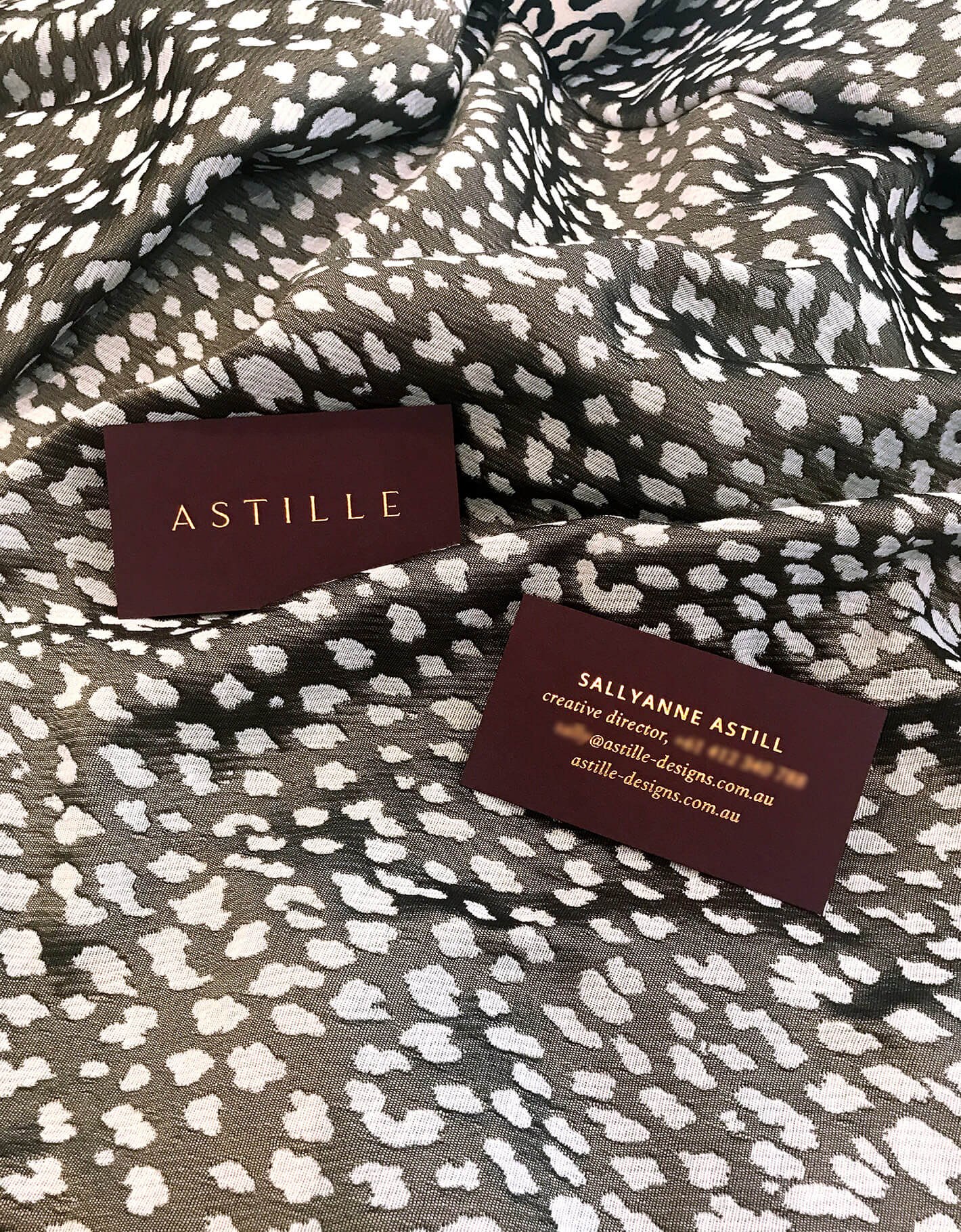 Astille copper foiled business cards on deep brown stock sit on leopard print fabric