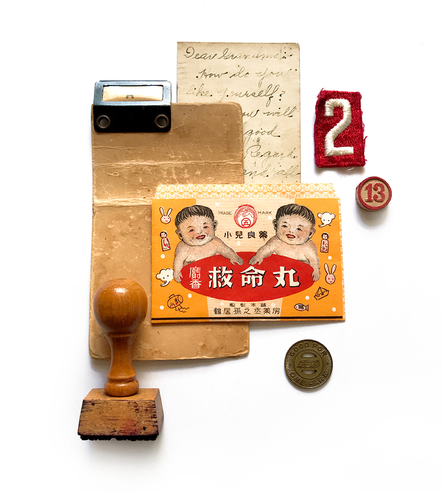photograph of found item collage of vintage objects like a vintage card, scout badge, stamp and japanese medicine envelope