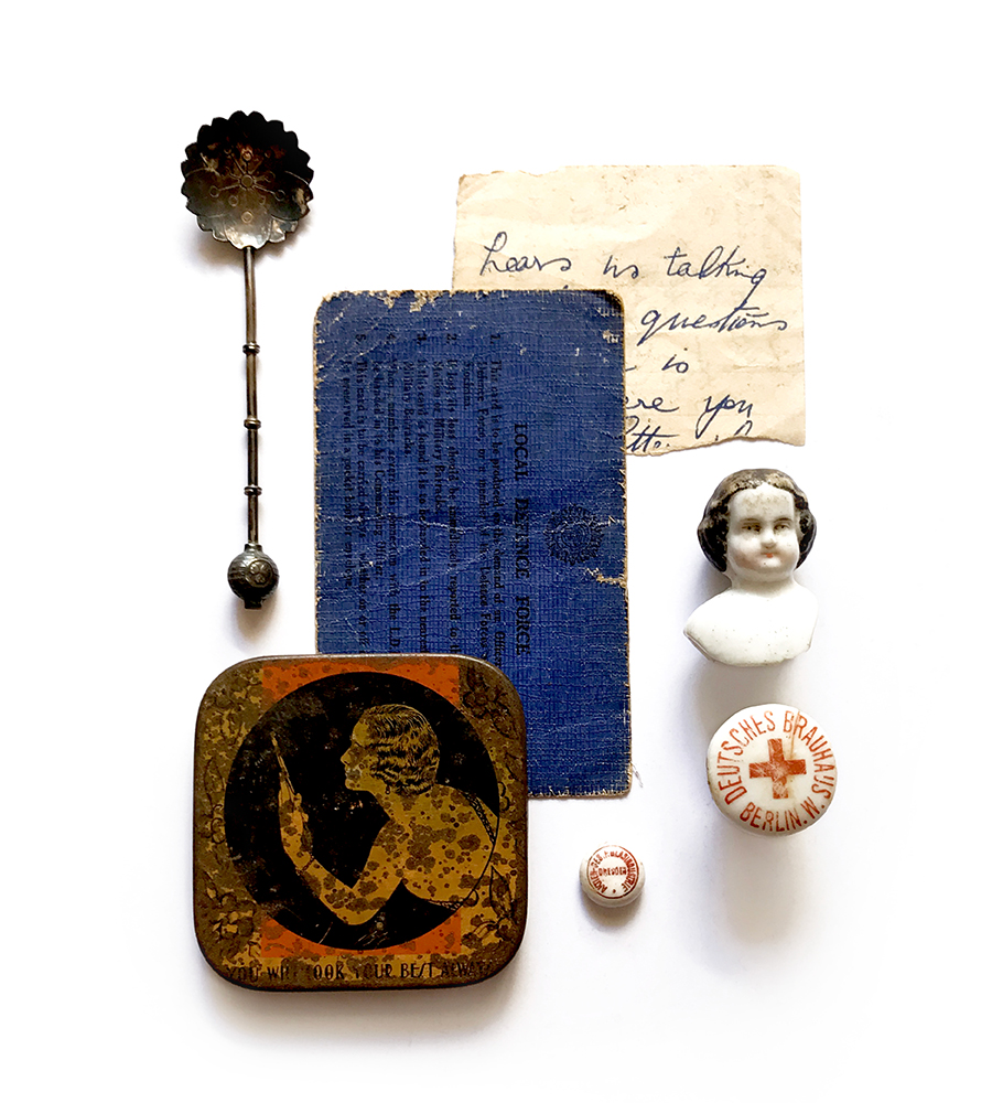 photograph of found item collage of vintage objects like a tin, spooon, doll head, hand written ephemera