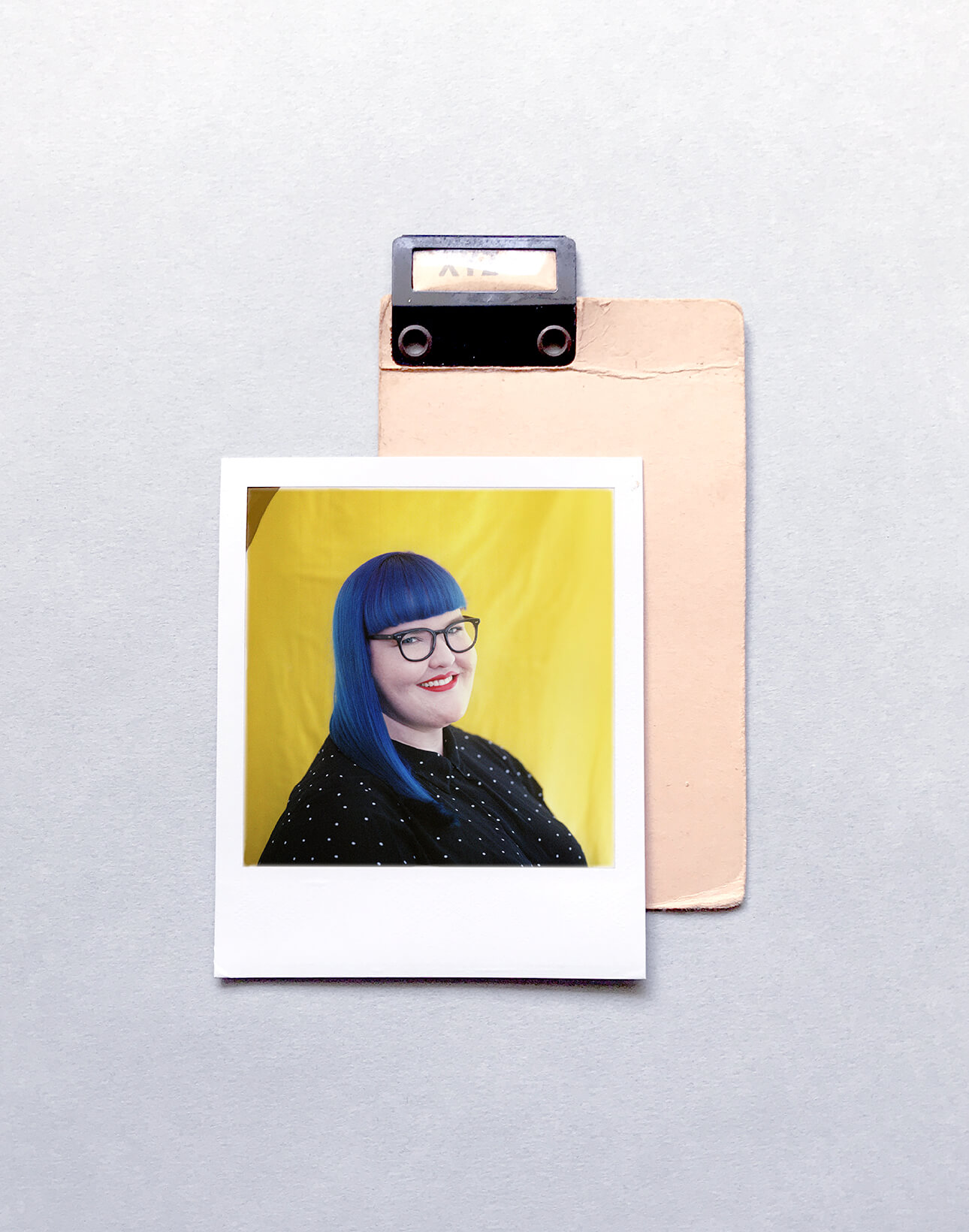Polaroid photo of designer laura from obscurio and co. She has bright blue hair and is in front of a yellow background
