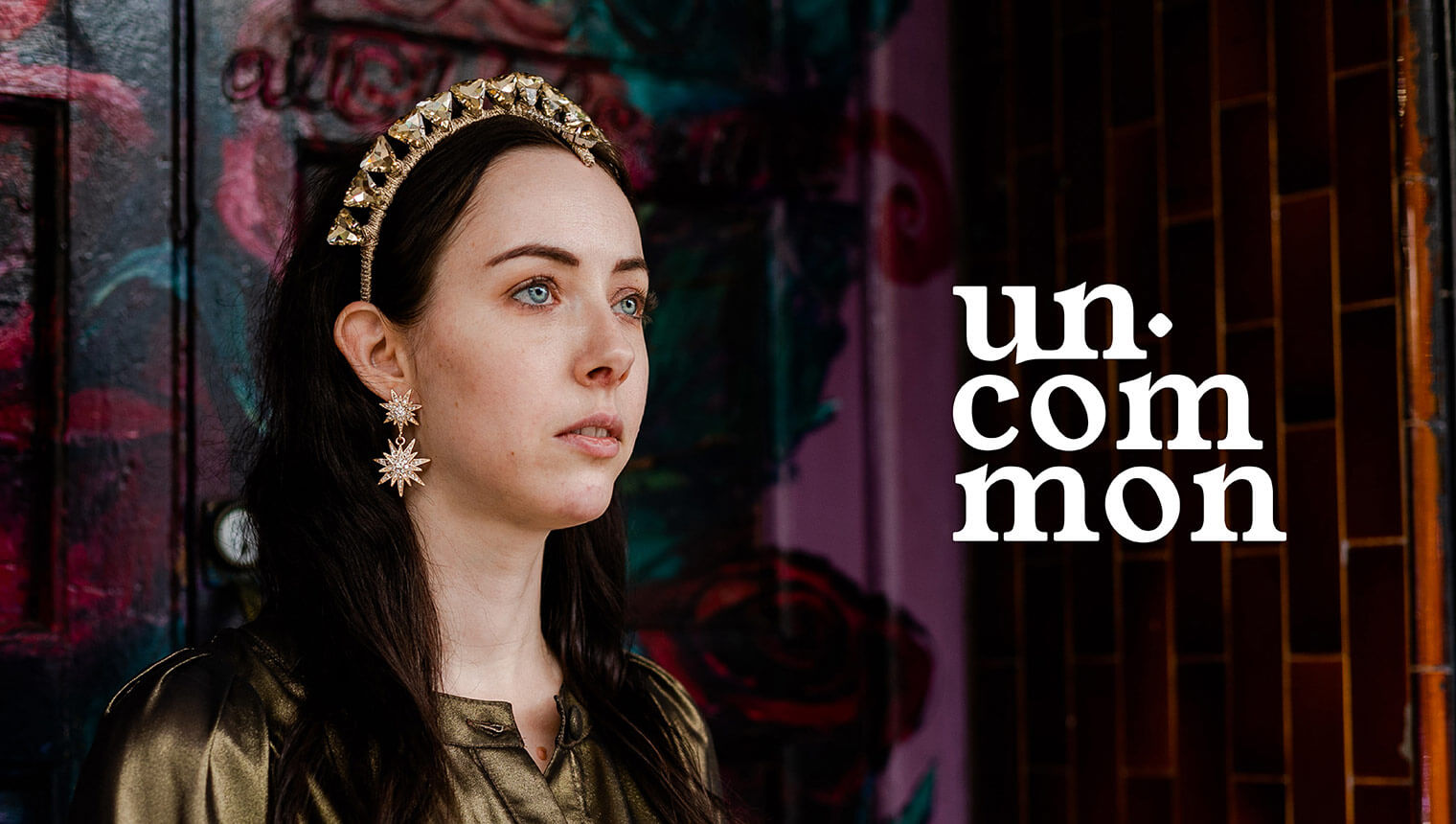 Woman in bold gold dress, crown and earrings alongside the uncommon stacked logo