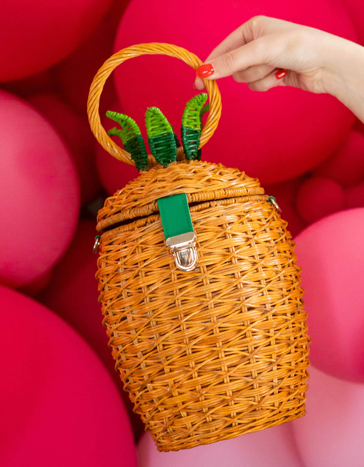 Image of pinapple-shaped wicker handbag with red balloons in the background