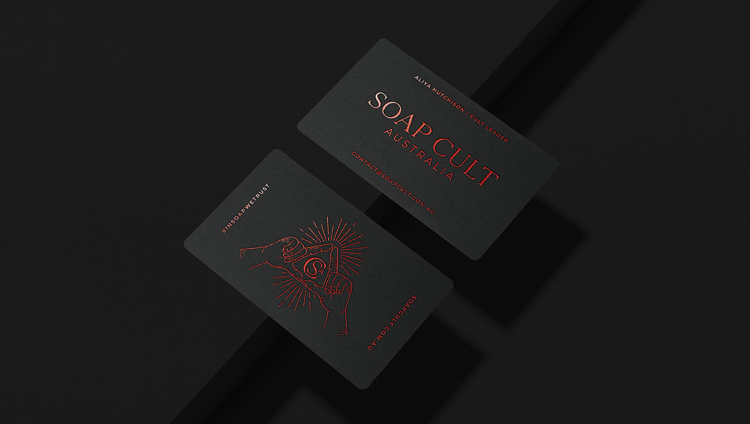 Black business cards with red foil and rounded corners sit on a black background. The details have a cult-like, occult feel.