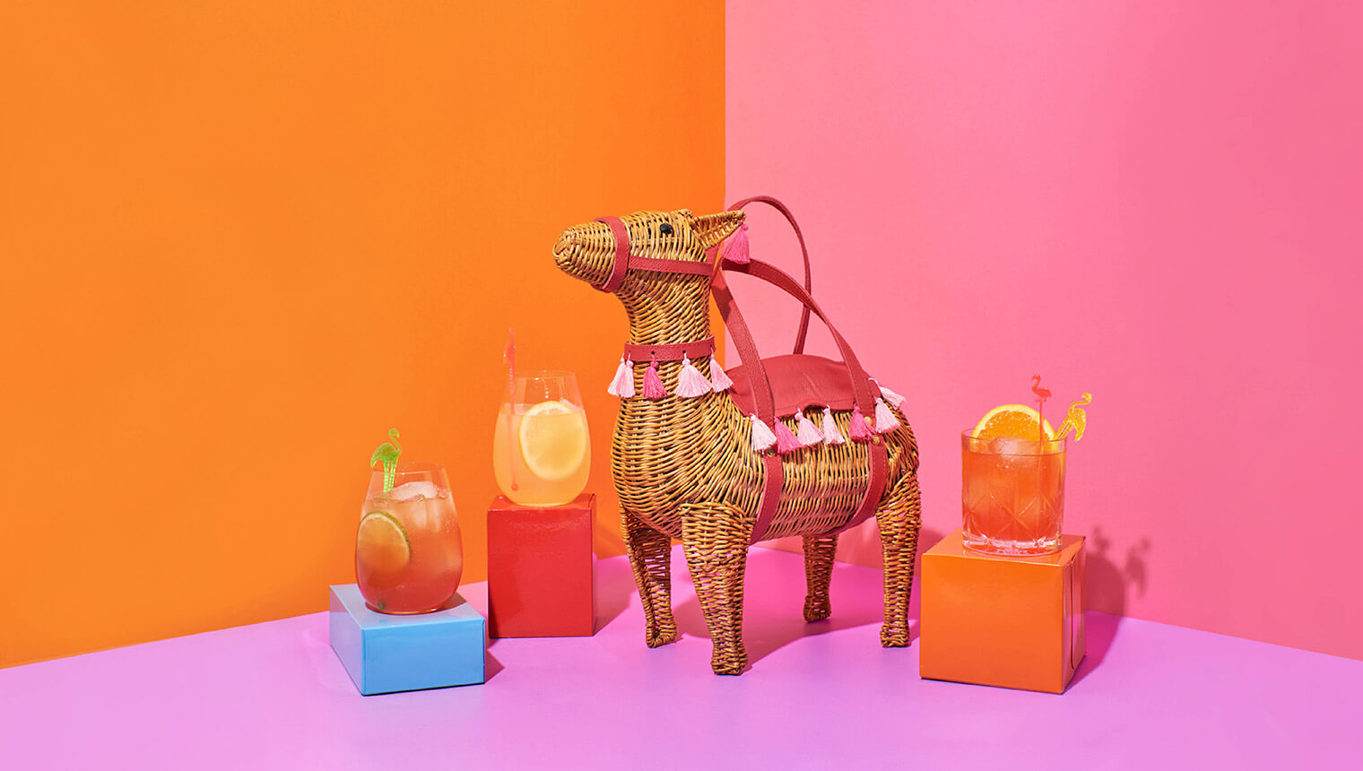 Bright orange and pink scene with llama shaped wicker handbag surrounded by cocktails