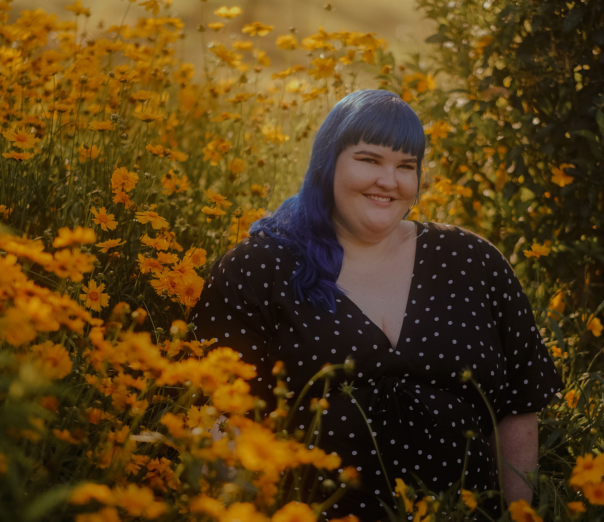 A plus sized woman with blue hair and a black dress with spots stands smiling in a field of yellow flowers